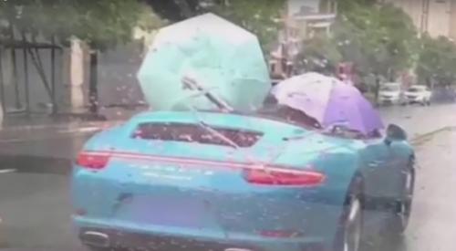 с зонтиком в кабриолете под дождём