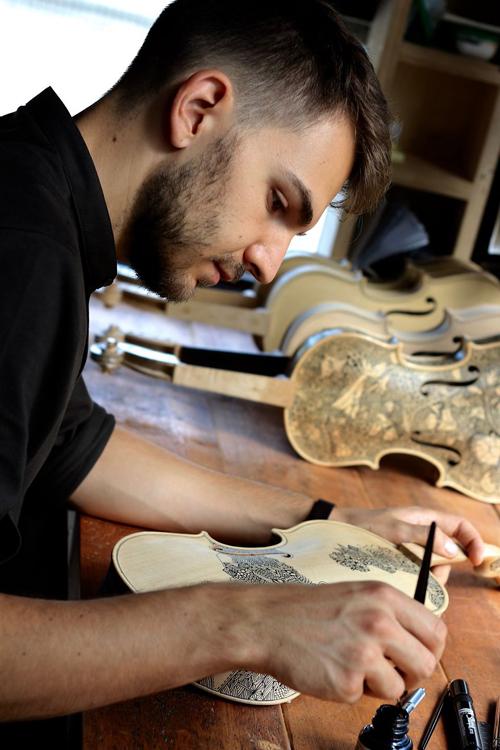 художник расписывает скрипки