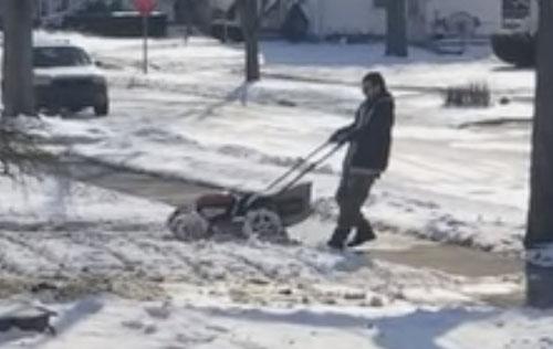 мужчина косит газон зимой