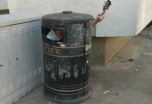 музыкант в урне для мусора