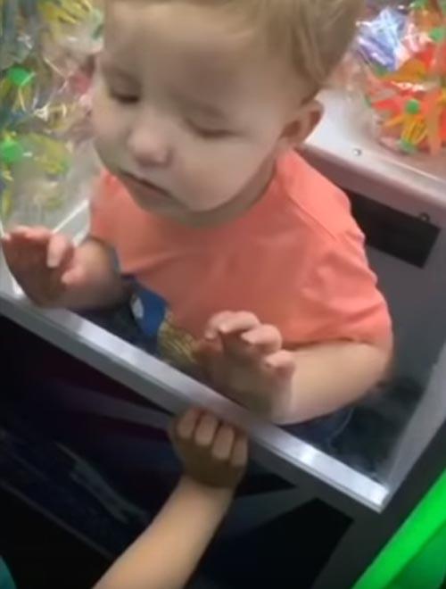 малыш в автомате с игрушками
