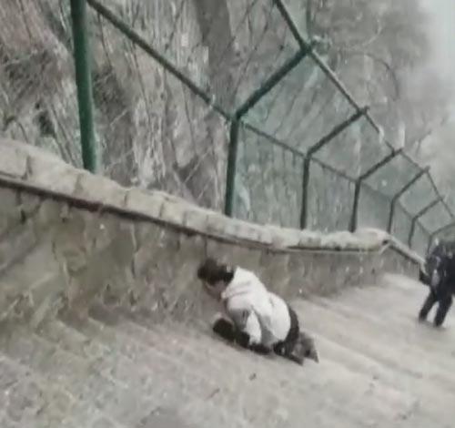 мужчина взбирается на вершину горы