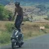 трюкач балансирует на скутере