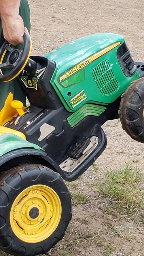 мальчик на игрушечном тракторе