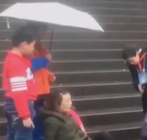 дети держат зонт над женщиной