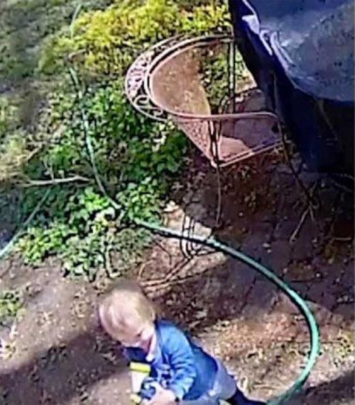 малыш играет со шлангом
