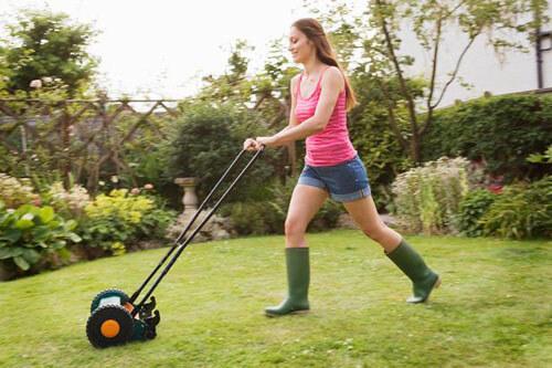 женщина косит газон утром