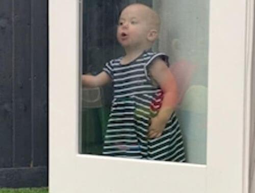 the baby behind the glass door