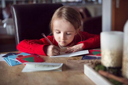девочка подписывает открытки