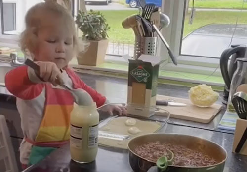 маленькая девочка готовит лазанью