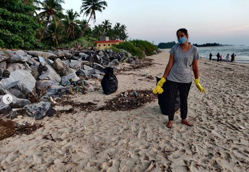 супруги убирают мусор с пляжа