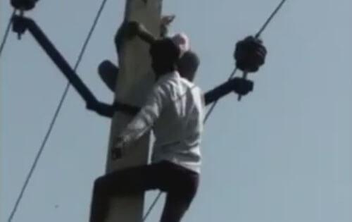 мужчина на электрическом столбе