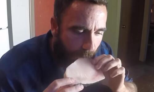 мужчина ест сырое мясо и рыбу
