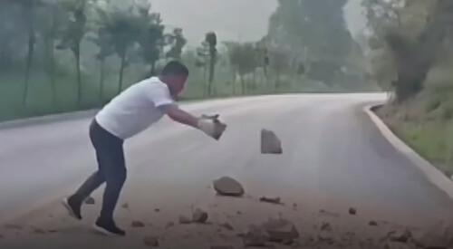 водитель убирает камни с дороги